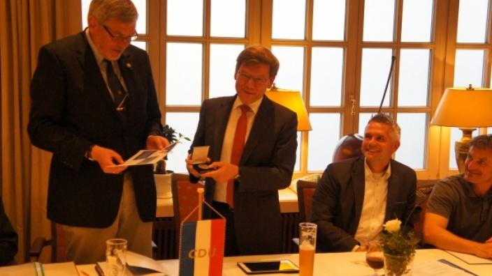 Horst Krebs (li.) erhält die Dankes-Medaille für 31 Jahre Ortsvorsitz in Nortorf